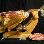 Jamón, jamonero, cuchillo, copa, plato de jamón, botella de vino, primer plano, estudio.